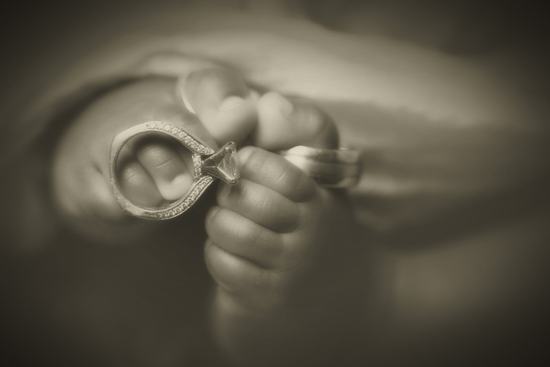 Vintage sepia tone portrait of a baby boy with wedding rings on his toes in the studio