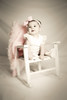 Vintage sepia tone portrait of a baby girl sitting in a chair in the studio