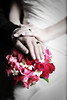 Stylized portrait of a newly wed couples hands with the rings over the bouquet.