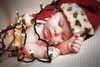 Stylized portrait of a baby boy in a santa hat with Christmas lights in the studio.