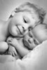 Black and white portrait of a young brother and infant sister snuggled up in the studio