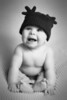 Stylized black and white portrait of a baby boy in an antler hat in the studio