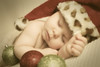 Stylized sepia tone portrait of a baby boy in a santa hat with ornaments in the studio.