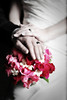 Stylized portrait of the bride and groom's hands with the rings over the bouquet.