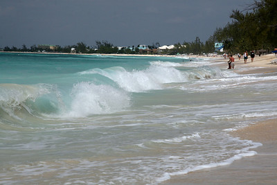 """Seven Mile beach kicks up playful waves during a winter """"nor'wester"""" storm."""