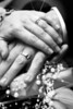 Stylized black and white portrait of a newly wed couples hands with the rings over the bouquet.