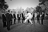 Stylized black and white portrait of a groom jumping in front of all the groomsmen at Lichterman Nature Center in Memphis, TN.