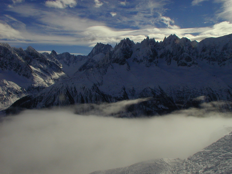 mountains and clouds<br /> And now for some clouds in the mountains!  This photo was taken on January 1, 2000 at  Chamonix, France.  The clouds were just spectacular and I stopped to take this photo.  Then I put my camera away, grabbed my ski poles, and skied down that slope right into the clouds.  I wish I could say I came out in one piece, but what I'll say instead is that when you ski on steep hills with moguls, it's really better if you can see well.  At least I like to think that's what caused my fall.  What I do know is that if you have to break your leg and need surgery on New Year's Day, Chamonix is a good place to do it - excellent doctors put me together almost as good as new.  The week stay in the hospital would have been a little better had I taken French rather than Spanish in school.  But all's well that ends well - I can still ski.