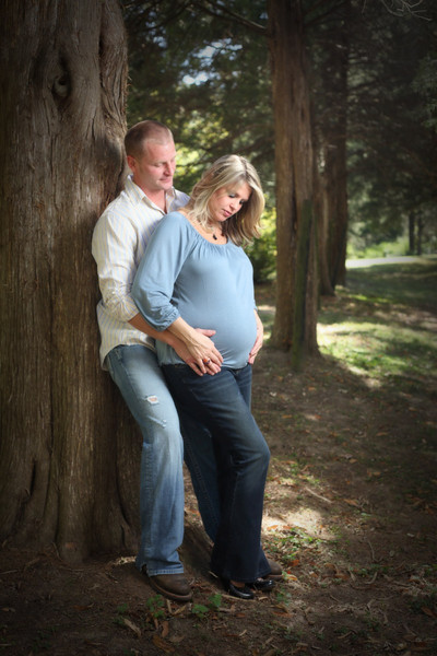 Maternity portrait of a husband and wife leaning against a tree in Germantown, Tennessee.
