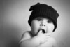 Black and white stylized portrait of a baby boy in a antler hat in the studio.