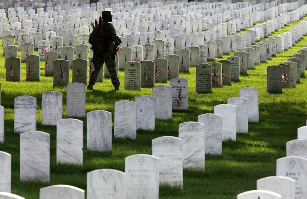 Army 1st Sargeant Shelly Jenkins places flags on graves at Arlington National Cemetery ahead of Memorial Day. (AP Photo/Jacquelyn Martin)