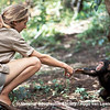 Young researcher Jane Goodall reaches out to touch hands with infant chimpanzee Flint.