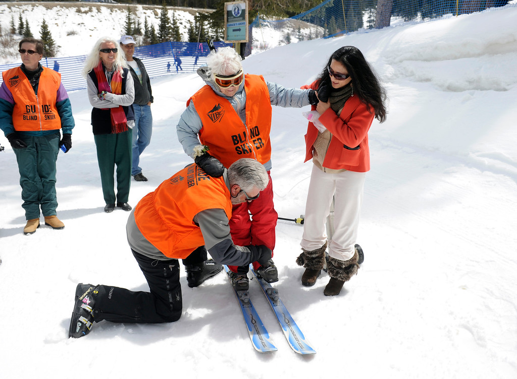 . SUMMIT COUNTY, CO - MAY 11: Elsa Bailey gets help from Leo Bush, left, and Lena Abboud, right, putting on her skis as he prepares to hit the slopes. Bailey has been a skier most of her life and after turning 100 years old, decided to celebrate by taking a run down a slope at Arapahoe Basin ski area. Dozens of family and friends joined her for a party and to witness this great physical feat. (Photo By Kathryn Scott Osler/The Denver Post)