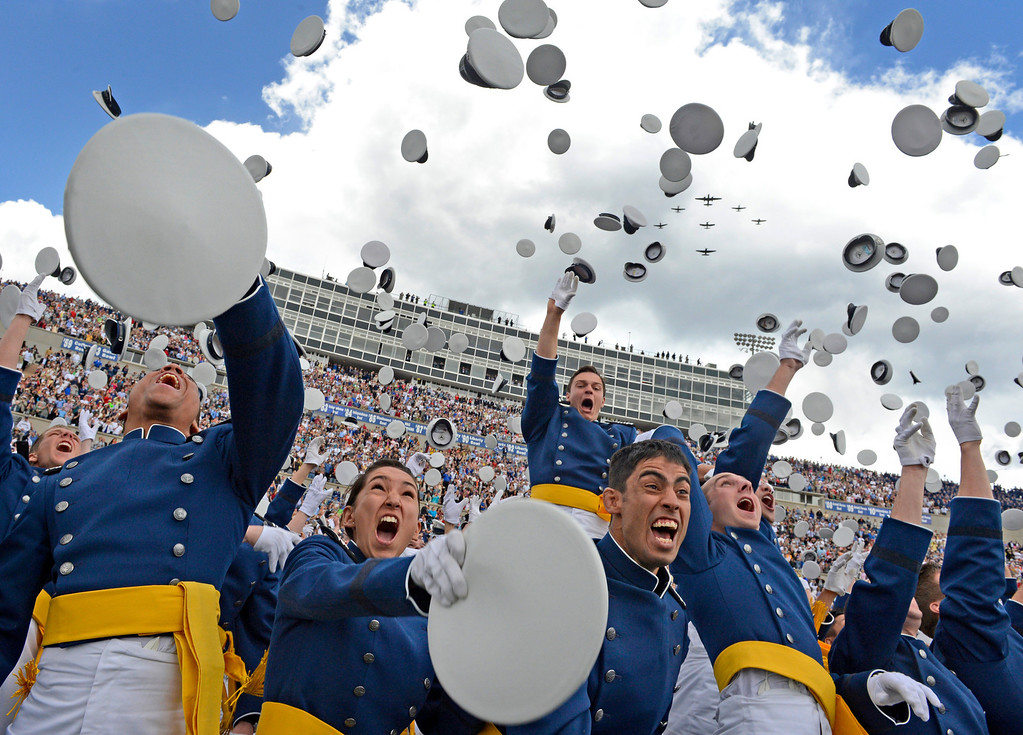 . Graduates toss their caps in the air as World War II aircrafts fly over head during the United States Air Force Academy graduation ceremony at Falcon Stadium in Colorado Springs, CO May 29, 2013. Secretary of the Air Force, Mr. Michael B. Donley presented diplomas to the, over 1000,  newly commissioned Second Lieutenants. (Photo By Craig F. Walker/The Denver Post)