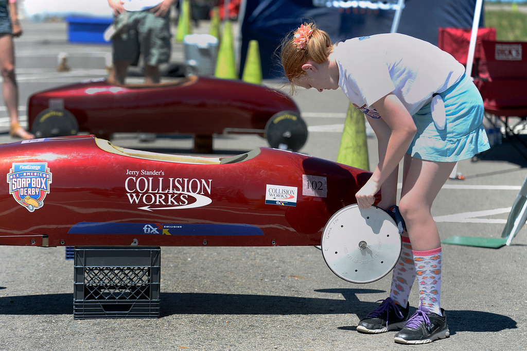 . Jenna Lee car #102 cleans her wheels before her next race at the Seventh Annual Sertoma Mile High Soap Box Derby June 9, 2013 in its first year at their new location at Arapahoe County Fair Grounds. The Sertoma Club, a non-profit international organization helps many of the estimated 50 million Americans with speech and hearing disorders. (Photo By John Leyba/The Denver Post)