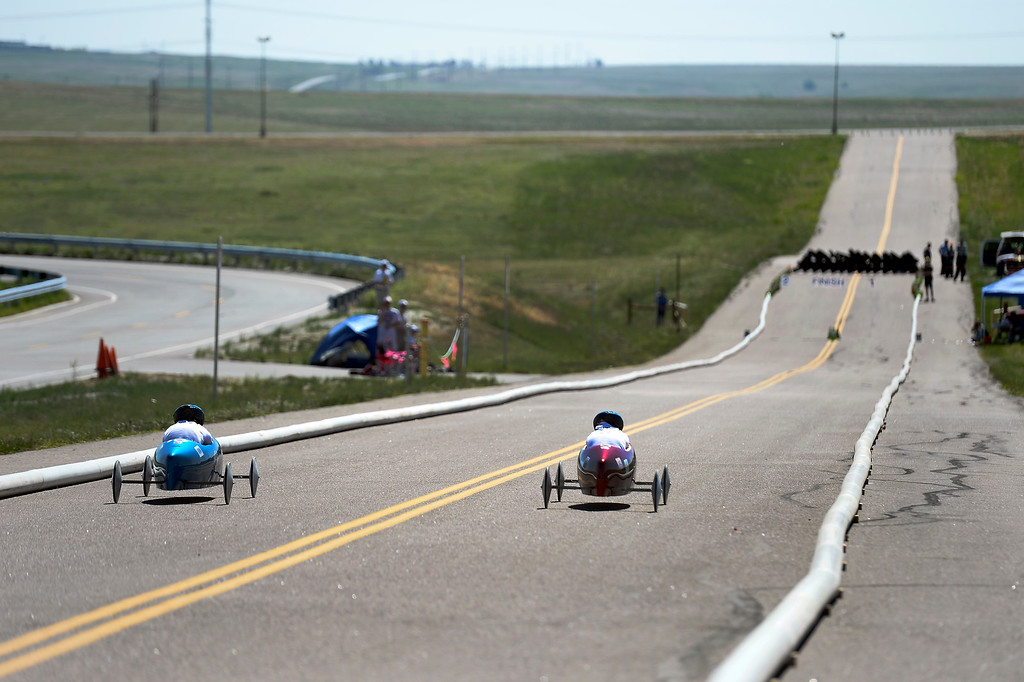 . Racers head down the track during their race at The Seventh Annual Sertoma Mile High Soap Box Derby. The Sertoma Club, a non-profit international organization, helps many of the estimated 50 million Americans with speech and hearing disorders. (Photo By John Leyba/The Denver Post)