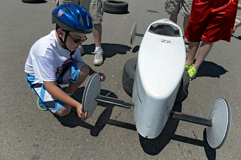 . Aaron Grument car #22 puts on his wheels before his race at the Seventh Annual Sertoma Mile High Soap Box Derby June 9, 2013 in its first year at their new location at Arapahoe County Fair Grounds. The Sertoma Club , a non-profit international organization helps many of the estimated 50 million Americans with speech and hearing disorders. (Photo By John Leyba/The Denver Post)