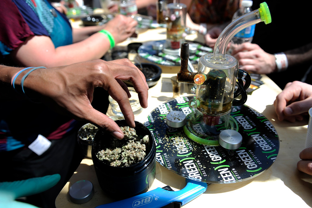 . Dominique Houston, 24, of Denver, packs a bowl for an attendee to sample at the Green Solution booth during the High Times Cannabis Cup at Denver Mart in Denver, Colorado on April 20, 2014. Event organizers are expecting 37,000 people to attend the two day cup in Denver. (Photo by Seth McConnell/The Denver Post)
