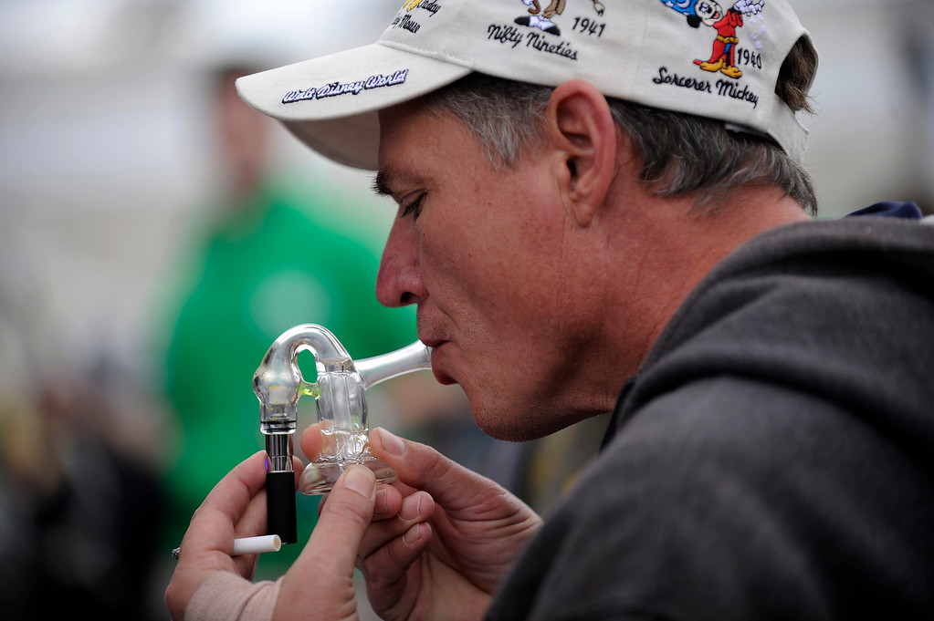. A man takes a hit off a bubbler vaporizer at the Vaped booth during the High Times Cannabis Cup at Denver Mart in Denver, Colorado on April 19, 2014.  (Photo by Seth McConnell/The Denver Post)