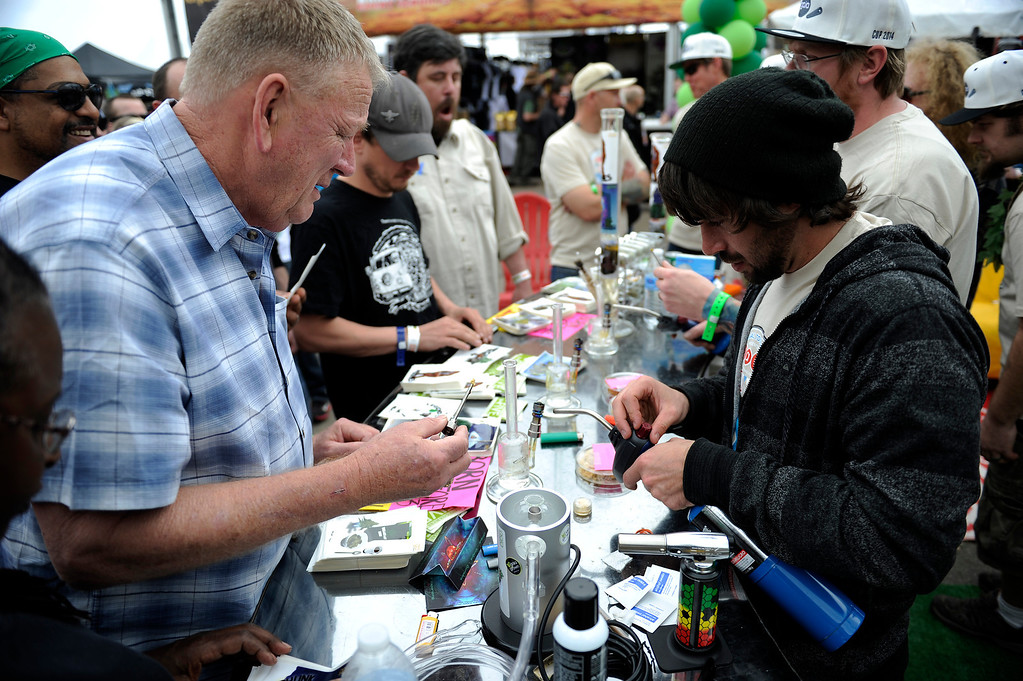 . Chris Bagley, left, loads up a dab for a client at the Gaia booth during the High Times Cannabis Cup at Denver Mart in Denver, Colorado on April 19, 2014.  (Photo by Seth McConnell/The Denver Post)