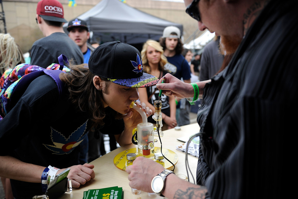 . A customer samples a dab at the Green Solution booth during the High Times Cannabis Cup at Denver Mart in Denver, Colorado on April 19, 2014. Event organizers are expecting 37,000 people to attend the two day cup in Denver. (Photo by Seth McConnell/The Denver Post)