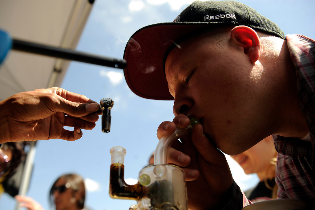 . Craig Mann, 25, of Denver, Colorado, samples the goods at the Green Solution booth during the High Times Cannabis Cup at Denver Mart in Denver, Colorado on April 20, 2014. Event organizers are expecting 37,000 people to attend the two day cup in Denver. (Photo by Seth McConnell/The Denver Post)