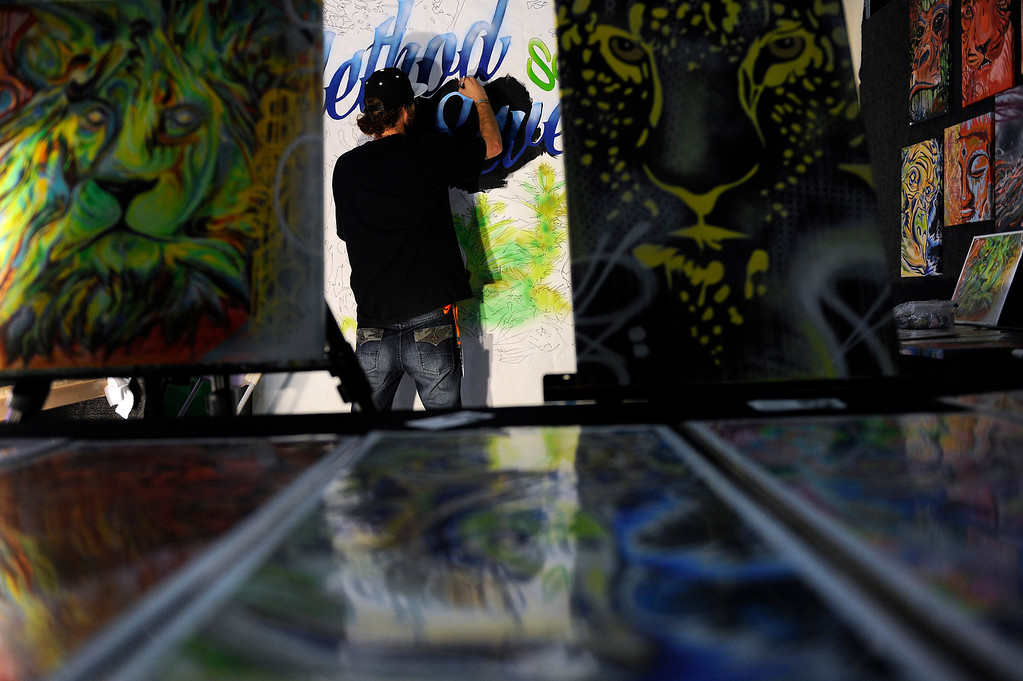 . Taylor Reinhold of Made Fresh Crew paints a mural at the Method Seven booth during the High Times Cannabis Cup at Denver Mart in Denver, Colorado on April 19, 2014.  (Photo by Seth McConnell/The Denver Post)