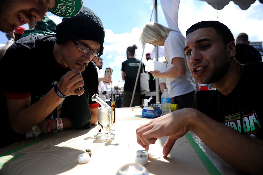. Lee Jones, 21, left, smells a bud as he chats with Gabriel Swint, 19, at the Grand Daddy Genetics booth during the High Times Cannabis Cup at Denver Mart in Denver, Colorado on April 20, 2014. Event organizers are expecting 37,000 people to attend the two day cup in Denver. (Photo by Seth McConnell/The Denver Post)