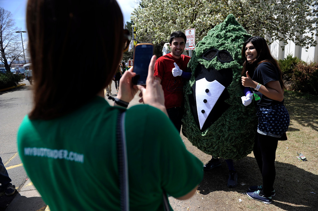 . People pose with a person dressed as a giant bud of marijuana during the High Times Cannabis Cup at Denver Mart in Denver, Colorado on April 20, 2014. Event organizers are expecting 37,000 people to attend the two day cup in Denver. (Photo by Seth McConnell/The Denver Post)
