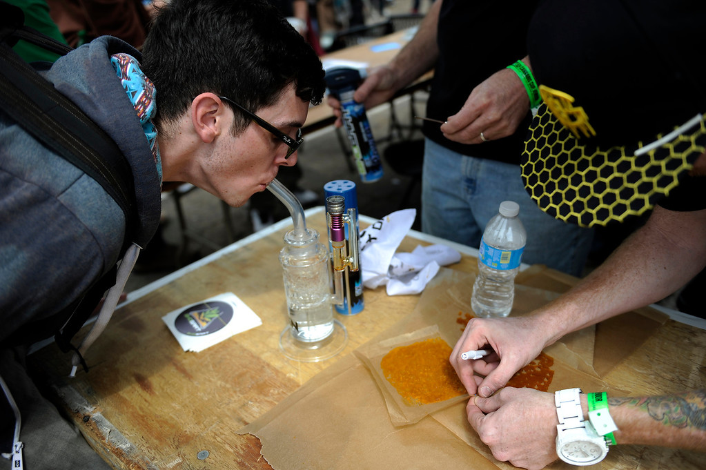 . A customer samples a dab at the Bhogart booth during the High Times Cannabis Cup at Denver Mart in Denver, Colorado on April 19, 2014.  (Photo by Seth McConnell/The Denver Post)