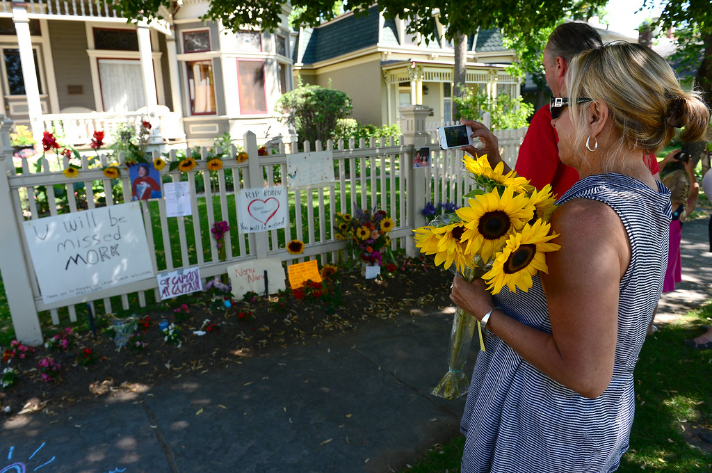 . Colleen Gleason came all the way from Fort Collins to leave sunflowers along the fence  of the Mork and Mindy house at 1619 Pine Street in Boulder, CO on August 12, 2014.   (Photo By Helen H. Richardson / The Denver Post)