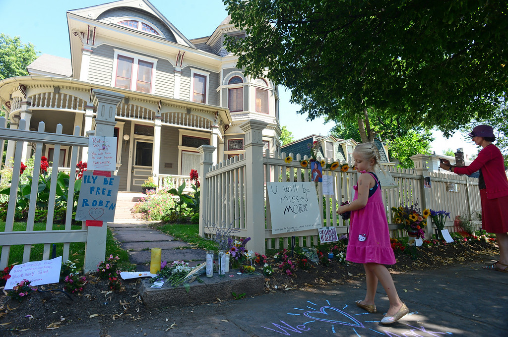 . Raleigh Hunnicutt, 5, gets ready to take a picture of all of the flowers, notes, cards, pictures, candles and drawings left in front of the Mork and Mindy house at 1619 Pine Street in Boulder, CO on August 12, 2014.(Photo By Helen H. Richardson / The Denver Post)