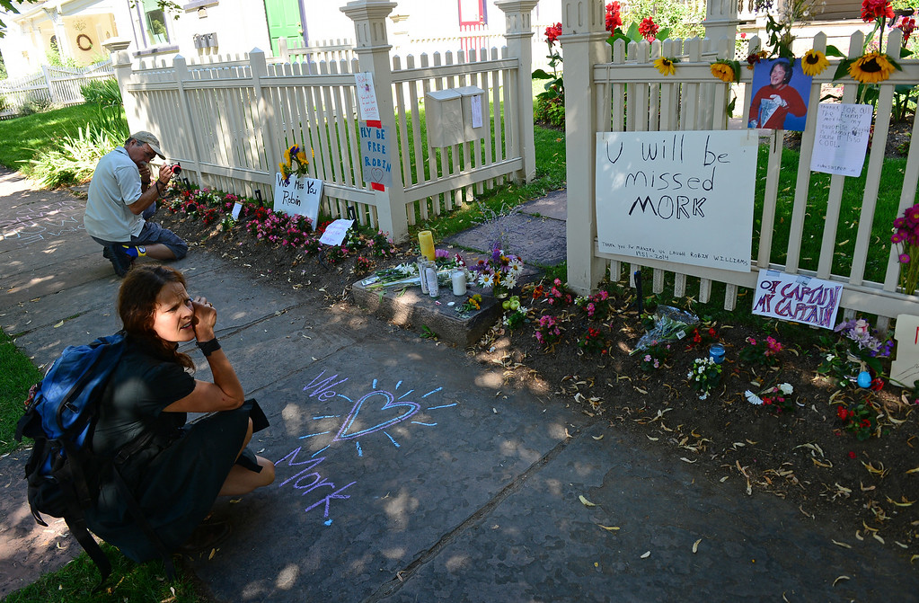 . Ashleigh Jai Hitchcock, left, pauses as she uses a pastel crayon to make a heart on the side walk outside in front of the Mork and Mindy house at 1619 Pine Street in Boulder, CO on August 12, 2014 in honor to of Robin Williams who died of an apparent suicide at his home in California. (Photo By Helen H. Richardson / The Denver Post)