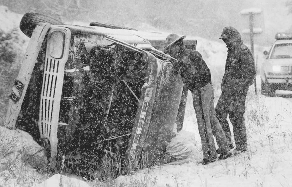 . NOV 30 1983  Snow storm Nov 8th accident I-70 near Idaho Springs. State patrol officer looks into the cab of a roll over pick-up as the driver watches. No injuries. Hazardous conditions truck went out of control.  Credit: The Denver Post