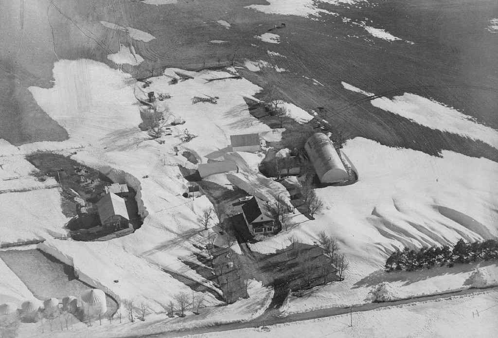 """. MAR 16 1977  Snowdrifts Create Wall Around Farm In Eastern Colorado Near Yuma \""""Capricious\"""" blizzard piled mountain of snow around buildings while leaving nearby land sparsely covered.  Credit: Denver Post Photo"""
