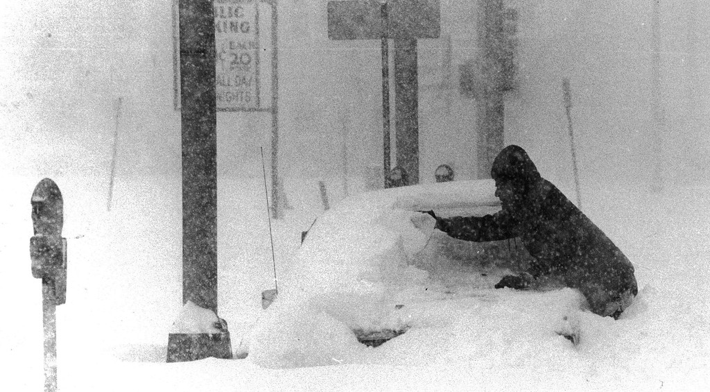 . 12/1982, 8/9/1992, DEC 24 1994  Jim Haldiman used a piece of card board to take the snow off his car on 15th St. at California. He needed to go home to get some medicine for his wife.  Credit: The Denver Post