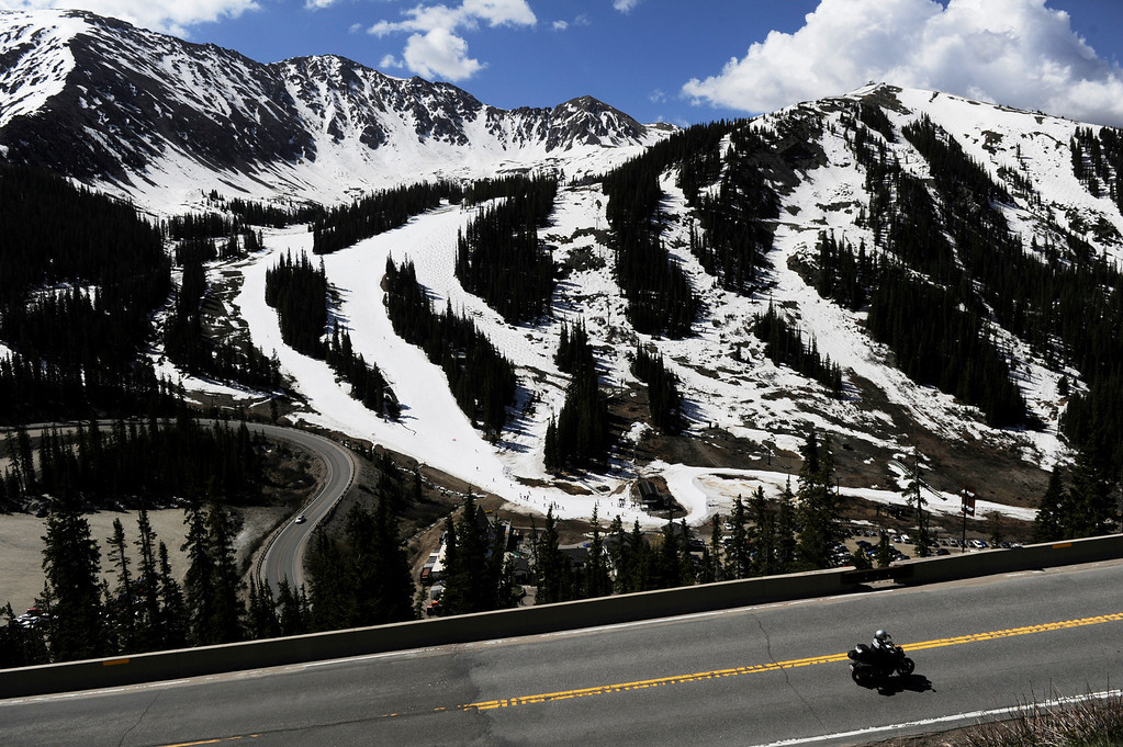 . SUMMIT COUNTY, CO - JUNE 08: A motorcycle rider rides up Loveland Pass, past the Arapahoe Ski Area in Summit County Colorado, Saturday morning, June 08, 2013.  The ski area will close for the season at the end of the day, Sunday June 09, 2013.  (Photo By Andy Cross/The Denver Post)