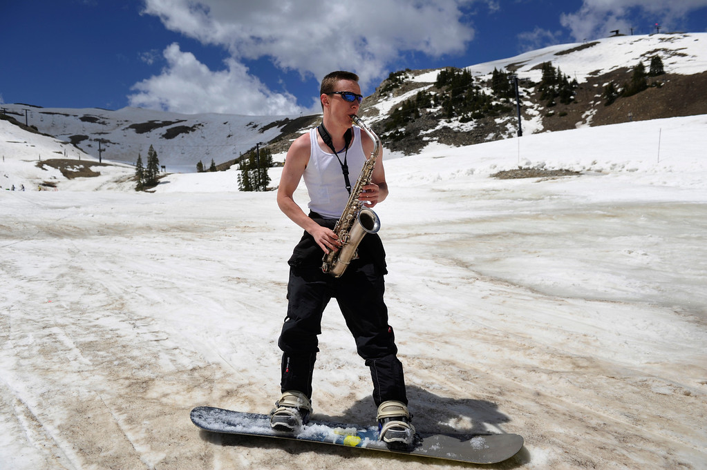 . SUMMIT COUNTY, CO - JUNE 08: Recent Metro State University of Denver graduate, Dan Ausmus, plays an old saxophone, era 1919, while snowboarding at the Arapahoe Basin ski area in Summit County Colorado, Saturday morning, June 08, 2013. The ski area will close for the season at the end of the day, Sunday June 09, 2013.  (Photo By Andy Cross/The Denver Post)