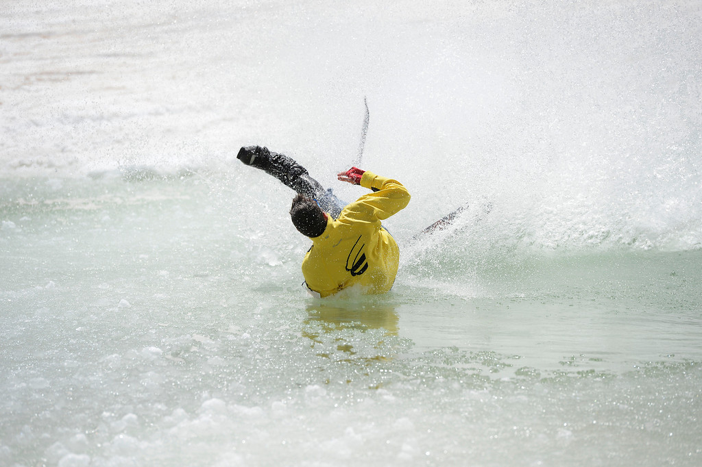 . SUMMIT COUNTY, CO - JUNE 08: Skier, Dave Overton, unsuccessfully tries to skim a natural pond that gathered with ice-cold water near the Dercum\'s Gulch area at the Arapahoe Basin ski area in Summit County Colorado, Saturday morning, June 08, 2013. Skiers and snowboarders alike challenged the pond, some making it some crashing and getting very wet. The ski area will close for the season at the end of the day, Sunday June 09, 2013.  (Photo By Andy Cross/The Denver Post)