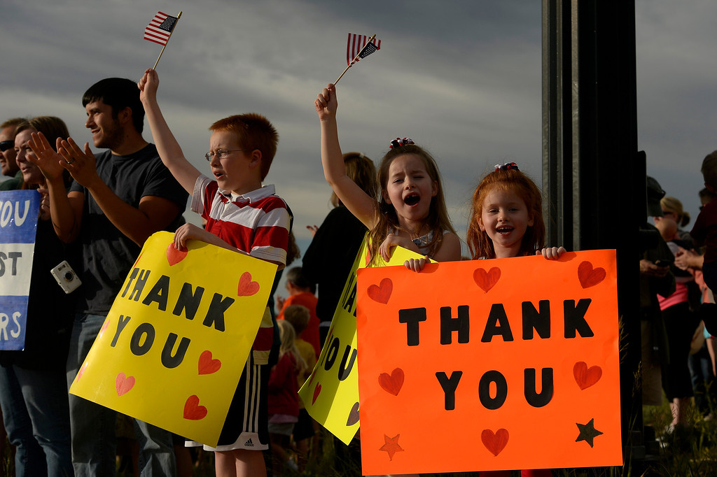 . BLACK FOREST, CO - JUNE 16:  From left to right siblings Braeden Weaver, 10 and his sisters Abby and, 7, and Emma, 5 hold up hand made signs with dozens of Colorado Springs and area residents who turned out at the corner of Old Ranch Road and Thunder Mountain Road outside of the Black Forest Fire Incident Command Post to cheer on firefighters and law enforcement officials as they come off of the fire line for the evening on June 16, 2013. The command post is set up at Pine Creek High School. The fire is currently 65% contained.  Photo by Helen H. Richardson/The Denver Post)
