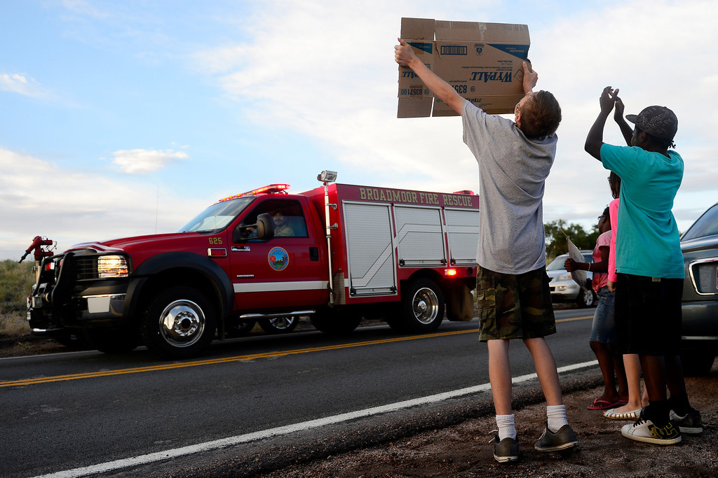 . Brothers Jonah (left) and Henry Butterfield join crowds in welcoming fire crews and other public officials back to the incident command post at Pine Creek High School as shifts change. The brothers\' father, Chris Butterfield, is a member of the 1157 Army National Guard fire crew. (Photo by AAron Ontiveroz/The Denver Post)