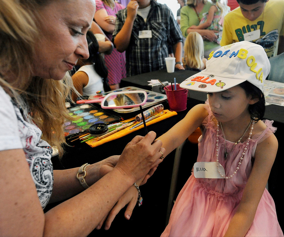 """. Ella Weigel, 7, right, gets her arm painted during Children\'s Hospital Colorado\'s \""""Take Me Out to the Ballgame\"""" cancer survivor\'s event on June 23, National Cancer Survivors\' Day, at the Children\'s Hospital in Aurora, Colo. Weigel, who was diagnosed with myelodysplastic syndrome (MDS - a condition in which blood-forming cells in the bone marrow are damaged), received a bone-marrow transplant from her brother over a year ago, and has been in remission since. Photo by Jamie Cotten, Special to The Denver Post"""