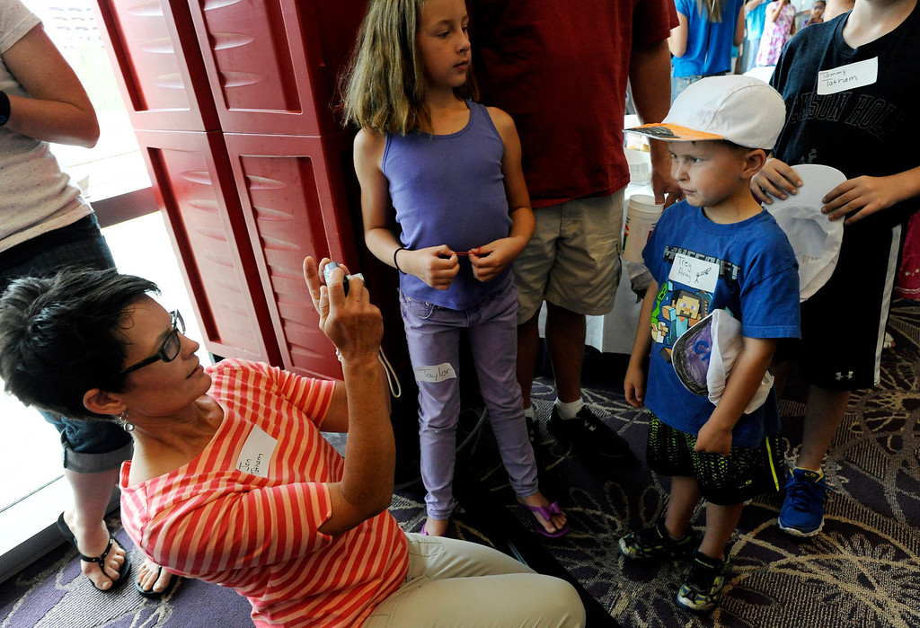 """. Jen Tatham, left, takes a photo of her son, Trey, 6, right, during Children\'s Hospital Colorado\'s \""""Take Me Out to the Ballgame\"""" cancer survivor\'s event on June 23, National Cancer Survivors\' Day, at the Children\'s Hospital in Aurora, Colo. Trey, who was diagnosed with a type of sarcoma (cancer of soft tissue, connective tissue or bone), has been in remission for over a year. Photo by Jamie Cotten, Special to The Denver Post"""