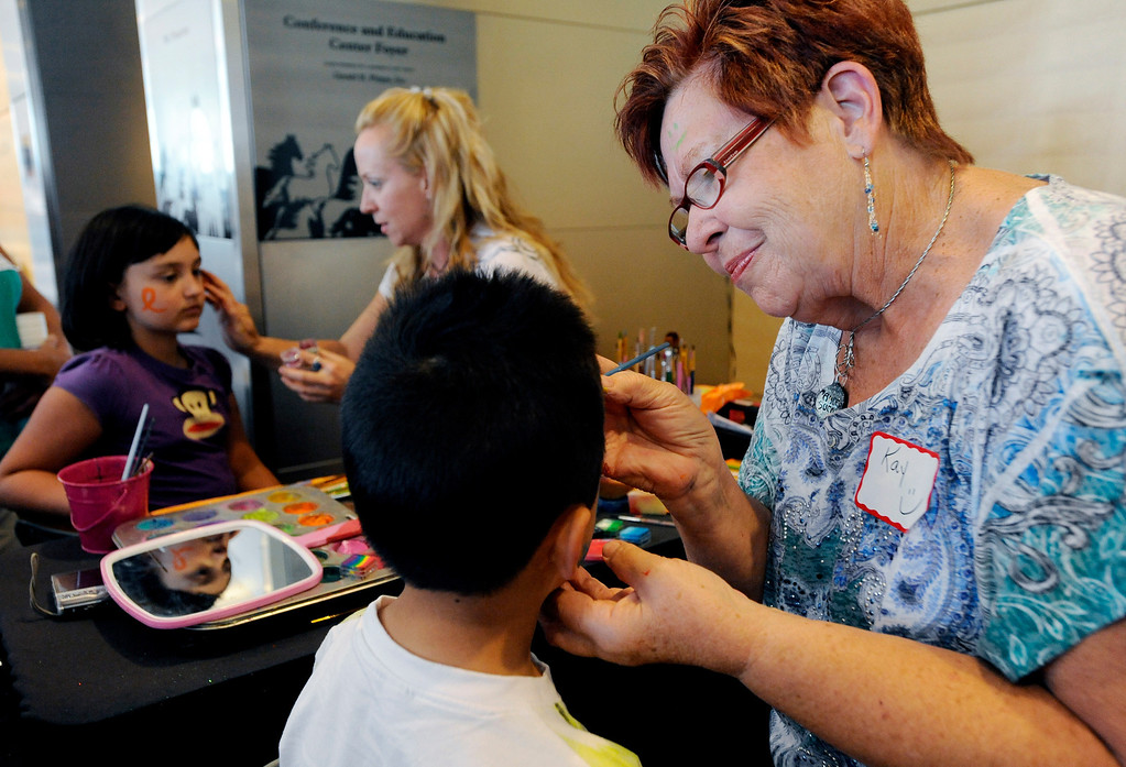 """. Kay Anderson, right, paints faces with her daughter, Tiffany Koehn, center, for a group of around 150 people - cancer survivors and their families - during Children\'s Hospital Colorado\'s \""""Take Me Out to the Ballgame\"""" cancer survivor\'s event on June 23, National Cancer Survivors\' Day, at the Children\'s Hospital in Aurora, Colo. Anderson, who was diagnosed with breast cancer in 2008 and who has been cancer free for over two years, decided she wanted to start painting faces when she found out she\'d lose her hair. Koehn painted her mother\'s head over 200 times during Anderson\'s treatment. Photo by Jamie Cotten, Special to The Denver Post"""