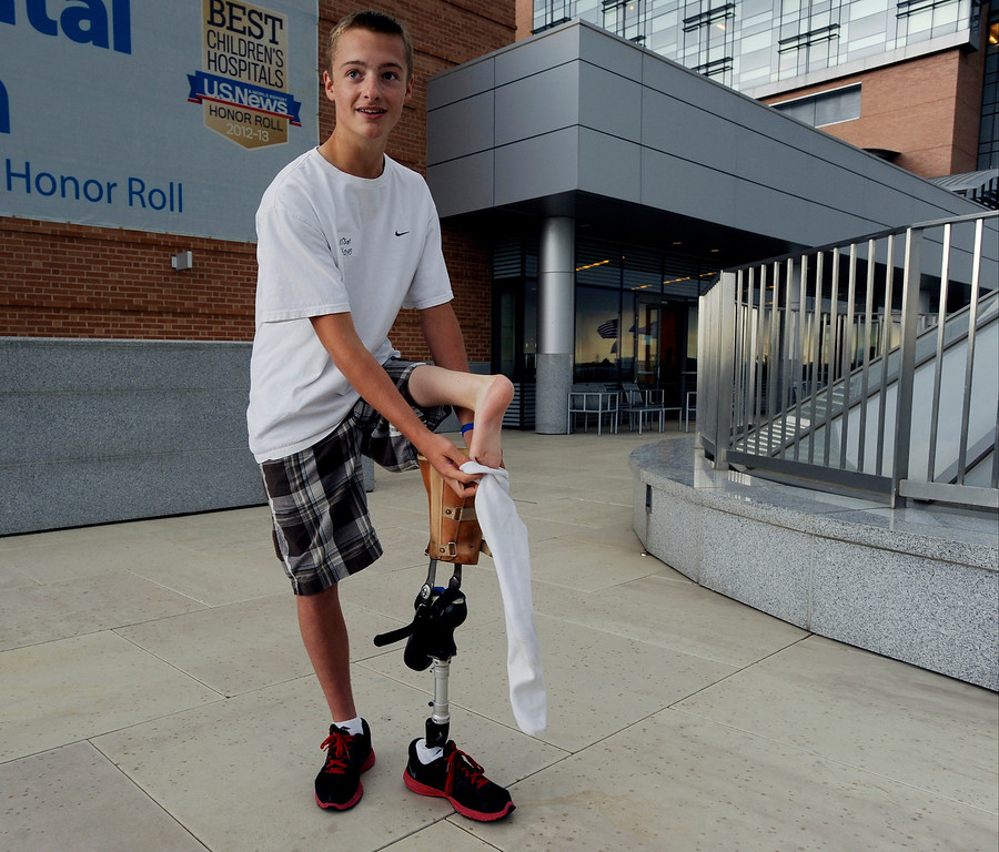 """. Garrison Hayes, 14, explains the surgery he received that helped to make him cancer free during Children\'s Hospital Colorado\'s \""""Take Me Out to the Ballgame\"""" cancer survivor\'s event on June 23, National Cancer Survivors\' Day, at the Children\'s Hospital in Aurora, Colo. Hayes was diagnosed with a type of sarcoma (cancer of soft tissue, connective tissue or bone) when he was six-years old, and after a surgery that substituted his ankle for his knee, is cancer free and plans to partake in paralympics in the near future. Photo by Jamie Cotten, Special to The Denver Post"""