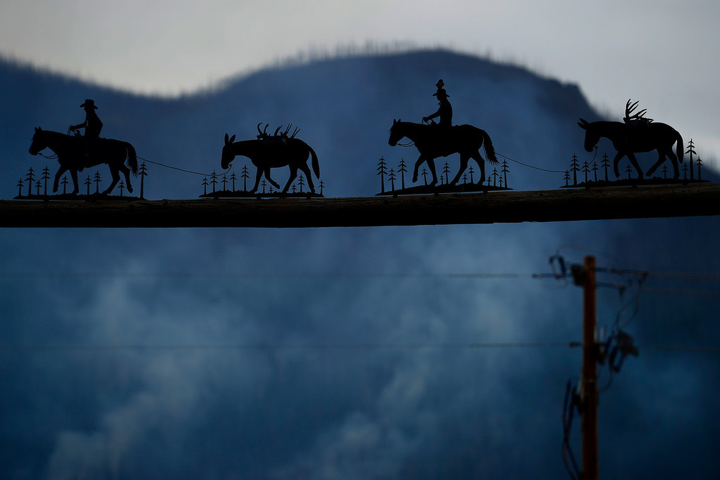 . The trees smolder behind the gate of the Freemon Ranch as the Papoose fire continues to burn near Creede. The three fires that make up the West Fork Complex fire now top out at more than 70 thousand acres. (Photo by AAron Ontiveroz/The Denver Post)