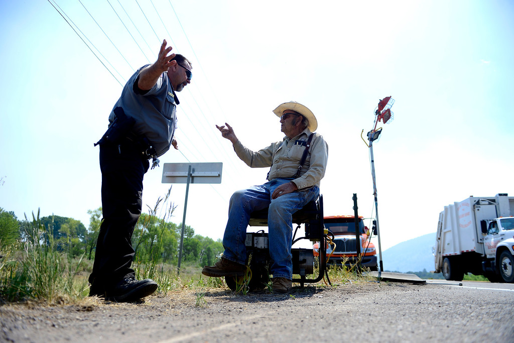. Deputy Boyd Wheel Wright of the Rio Grande County Sheriff\'s office asks landowner Vernon Mann why he needs to cross the road blockade on Highway 160 as the West Fork Fire continues to burn near South Fork. The West Fork Fire grew to more than 70,000 acres overnight. (Photo by AAron Ontiveroz/The Denver Post)