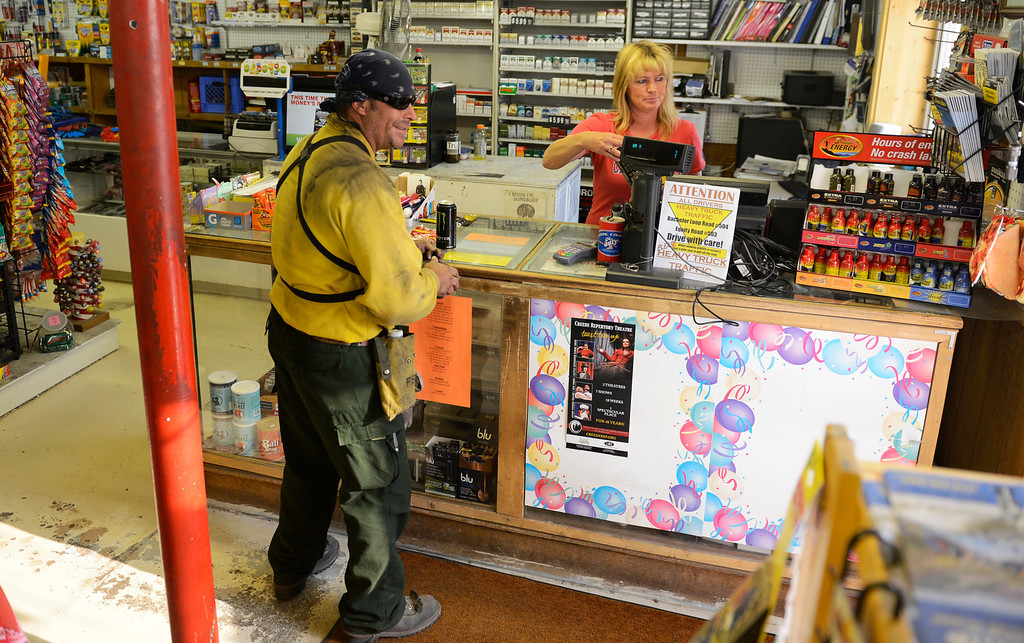 . CREEDE, CO-June 27, 2013: Firefighter Michael Remero was all smiles after finding out his snacks and drink were free at Gifts and Gas in Creede, June 27, 2013. Vicki Vinyard, right who works in the store and other locals, put money into a fund to help pay for the goodies that firefighters are buying in the morning before heading back to the fire lines. (Photo By RJ Sangosti/The Denver Post)