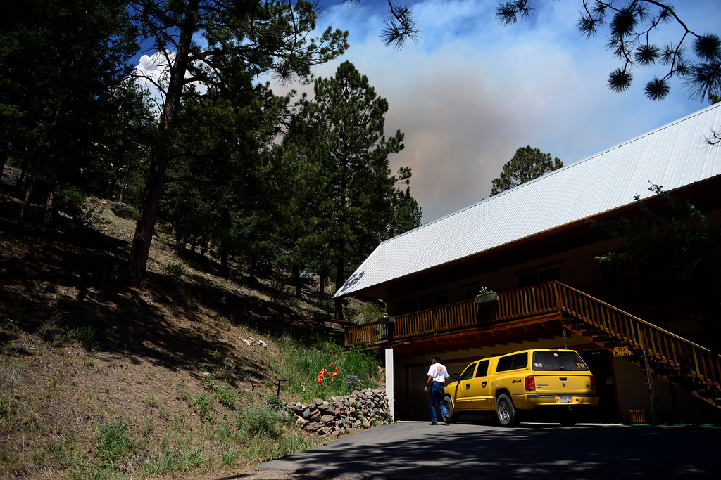 . Ron Marx stands outside of his home as a plume of smoke rises over the hill as the West Fork Fire continues to burn near South Fork. Marx and his wife, Bee, were allowed into their home for 15 minutes to gather items. The West Fork Fire grew to more than 70,000 acres overnight. (Photo by AAron Ontiveroz/The Denver Post)