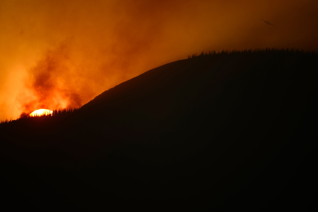 . CREEDE, CO - JUNE 25: A plane flies over before dropping slurry as the Papoose fire continues to burn at sunset near Creede. The three fires that make up the West Fork Complex fire now top out at more than 70 thousand acres. (Photo by AAron Ontiveroz/The Denver Post)